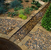 STONE-EDGED PEBBLE-FILLED RILL RUNS THROUGH THE EVENING STANDARD EROS GARDEN. CHELSEA 95. DES: JULIE TOLL