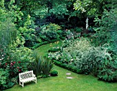 WHITE WOODEN BENCH ON LAWN WITH ROSES & PHORMIUM TENAX. BOX EDGED SILVER BORDER & PATH LEADS TO STATUE.DES:OLIVIA CLARKE