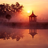 DAWN MIST: SUN RISES OVER CHINESE STYLE PAGODA BESIDE LAKE IN PRIVATE GARDEN.  CHASTLETON GLEBE OXFORDSHIRE