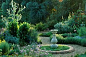 SUNDIAL IN CENTRE OF HERB GARDEN WITH CHAMOMILE  ALLIUM SCHOENOPRASUM  TEUCRIUM CHAMAEDRYS. COTON MANOR  NORTHANTS