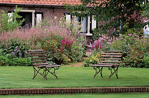 VIEW_TO_THE_FARMHOUSE_PAST_TWO_SEATS_INBG_IS_ASTILBE_VAR_TAQUETII_PURPURLANZE_DESIGNPIETANJA_OUDOLF_