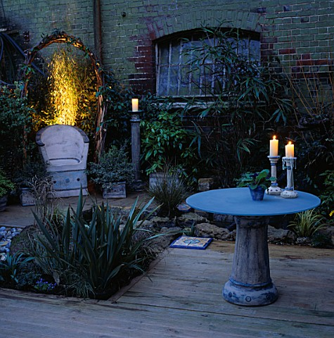 NIGHTLIT_CORNER_OF_GARDEN_WITH_CERAMIC_CHAIR__GLASSCERAMIC_TABLE_WITH_CANDLES_DESIGNER_EMMA_LUSH_WAT