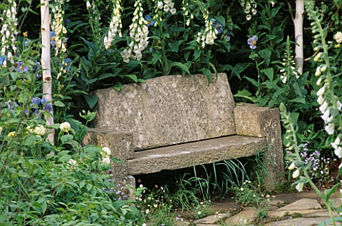 SIMPLE_STONE_SEAT_SURROUNDED_BY_FOXGLOVES_THE_EVENING_STANDARD_GARDEN_DESIGNER_XA_TOLLEMACHE_CHELSEA