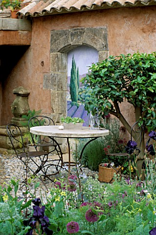 TABLE__CHAIRS_ON_COBBLE_TERRACE_WITH_TROMPE_LOEIL_PAINTING_BY_JOHN_SIMPSON_IN_BG_BSKYB_GARDEN_DESIGN