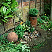 WATER FEATURE: WALL MOUNTED CERAMIC TOAD WATER SPOUT ABOVE BRICK EDGED PEBBLE POND. DESIGNER: LUCY SMITH