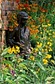 STATUE OF SMALL BOY AMIDST YELLOW PLANTING OF HELENIUMS  CROCOSMIA  COREOPSIS AND OENOTHERA IN THE RAILWAY CHILDRENS GARDEN  HAMPTON COURT 97. DESIGNER: PAUL STONE.