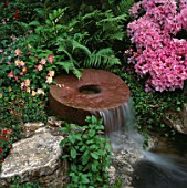 WATER FEATURE: MILLSTONE WATERFALL SURROUNDED BY FERNS  RHODODENDRONS AND AQUILEGIAS. DAILY MIRROR GARDEN  CHELSEA 1994