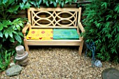 TROPICAL GARDEN WITH WOODEN BENCH AND BRIGHTLY COLOURED CUSHIONS  WITH BUDDHAS HEAD  WIRE BIRD  FATSIA JAPONICA  ARUNDINARIA NITIDA  ASPLENIUM SCOLOPENDRIUM. DESIGNER: ANDY REES