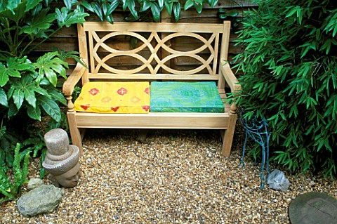 TROPICAL_GARDEN_WITH_WOODEN_BENCH_AND_BRIGHTLY_COLOURED_CUSHIONS__WITH_BUDDHAS_HEAD__WIRE_BIRD__FATS