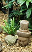 BUDDHAS HEAD IN THE TROPICAL GARDEN WITH FATSIA JAPONICA  ASPLENIUM SCOLOPENDRIUM. DESIGNER: ANDY REES