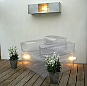 METAL CONTAINERS WITH WHITE NIGHT SCENTED STOCKS STAND BESIDE INFLATABLE   CHAIR ON WOODEN DECKING IN CHARLES WORTHINGTONS MINIMALIST GARDEN. (NIGHT-LIT) DESIGNER:STEPHEN WOODHAMS