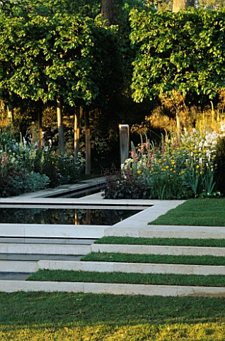 STEPPED_WATER_FEATURE_WITH_STONE_EDGING_AND_LAWN_METAL_RECTANGULAR_SCULPTURE_AS_FOCAL_POINT__EVENING