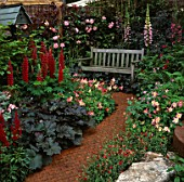 BRICK PATH LEADS THROUGH RED THEMED COTTAGE BORDERS OF LUPINS & AQUILEGIAS TO SECLUDED WOODEN BENCH. DESIGNER: JOHN PLUMMER. CHELSEA 1993