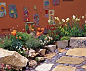 PUMPKIN COLOURED WALL WITH CERAMIC PICTURES. IN FOREGROUND ARE ORANGE TULIPS AND ARIZONA FLAG STONE AND MEXICAN COBBLES. KEEYLA MEADOWS  CALIFORNIA