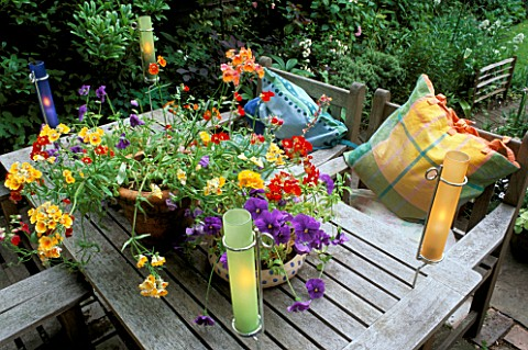 CANDLES_IN_COLOURED_GLASS_TUBES_LIGHT_UP__A_GROUP_OF_SUMMER_CONTAINERS_ON_TABLE_SEATS_WITH_CUSHIONS_