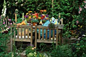 SHELTERED CORNER OF GARDEN WITH TABLE & CHAIRS. CANDLES IN COLOURED GLASS TUBES LIGHT UP COLOURFUL CUSHIONS & FLORAL ARRANGEMENT ON TABLE. DESIGNER: LISETTE PLEASANCE