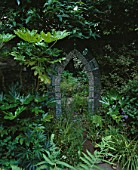 A MOSAIC MIRROR WITH SHELLS  PEBBLES AND TILES IS SURROUNDED BY HEDERA GOLDHEART  POLEMONIUM CAERULEUM  FATSIA JAPONICA AND FICUS BROWN TURKEY