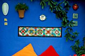 DECORATIVE FEATURE: BRIGHTLY COLOURED MOSAIC SET IN ULTRAMARINE BLUE WALL. BENEATH ON A WOODEN BENCH ARE ORANGE AND RED CUSHIONS. DESIGNERS: ANDREW AND KARLA NEWELL