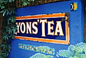 DECORATIVE FEATURE: A LYONS TEA SIGN  A MOSAIC AND A SMALL PAINTED MEXICAN TILE ON AN ULTRAMARINE BLUE WALL. DESIGN: ANDREW & KARLA NEWELL