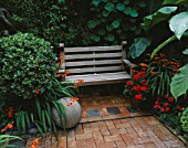BRICK COURTYARD WITH STONE BALL  CROCOSMIA AND WOODEN BENCH.  DESIGN: ANDREW & KARLA NEWELL