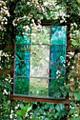 TURQUOISE STAINED GLASS PANEL BY JOANNA HARDING SURROUNDED BY JASMINUM OFFICINALE. DESIGNER: ALEX JEFFERSON.