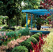 BLUE PAINTED PERGOLA OVER DECKING WITH BOX BALLS AND ASTILBES IN THE FOREGROUND. TO THE BACK IS A YELLOW CHILDRENS SLIDE. DESIGN BY DAVID STEVENS