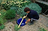 WATER FEATURE STEP-BY-STEP: LOUISE HAMPDEN CHECKS THAT THE BLUE PLASTIC BUCKET IS LEVEL USING A SPIRIT LEVEL