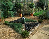 KNOT GARDEN WITH GRAVEL  PEBBLES  BLACK OPHIOPOGON GRASS  FESTUCA GLAUCA AND A GREEN GLAZED POT IN THE CENTRE