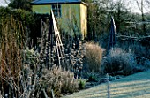 THE SUMMERHOUSE GARDEN AT ARROW COTTAGE IN THE FROST. BLUE WOODEN TRIPOD IN FOREGROUND AND THE TOWER BEHIND