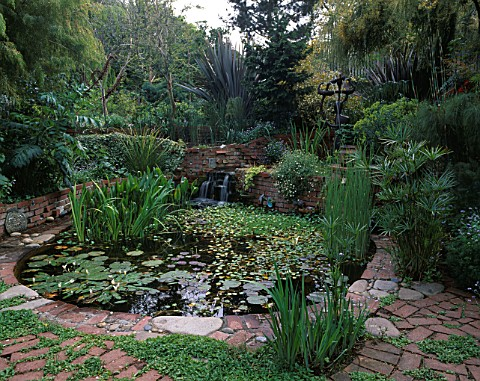LARGE_CIRCULAR_POOL_SURROUNDED_BY_LUSH_PLANTING_INCLUDING_PHORMIUMS_AND_BRONZE_FERTILITY_GODDESS_FOU