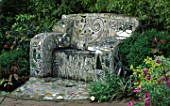 A CEMENT SOFA EMBROIDERED WITH MIRROR FRAGMENTS AND MARBLES IN ROBERT CLARKS SAN FRANCISCO GARDEN. THE SEAT WAS DESIGNED BY RAUL ZUMBA