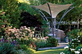 MODERN STEEL AND CANVAS CANOPY WHICH ACTS AS A PARASOL  RAINCATCHER AND SOLAR PANEL IN MODERN GARDEN. TELEGRAPH REFLECTIVE GARDEN  CHELSEA 99.