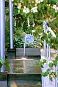 WATER FEATURE: STEPPED CANAL WITH CLASSICAL TRITON MASK WATER SPOUT SURROUNDED BY ARCHITECTURAL FORMS IN MODERN GARDEN. TELEGRAPH REFLECTIVE GARDEN  CHELSEA 99.