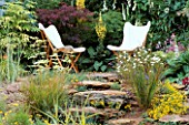 TWO BEAUTIFUL WHITE CANVAS DECKCHAIRS SURROUNDED BY SANDSTONE ROCKS AND MAPLES AND VERBASCUM. THE VERY INTERESTING LANDSCAPE COMPANY.