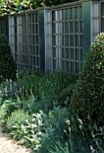 METAL AND WOOD TRELLIS SCREEN WITH GREY BORDER  TAXUS YEW TOPIARY AND PLATANUS ACERIFOLIA. CHRISTIES SCULPTURE IN THE GARDEN  CHELSEA 99