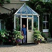 JENNY JOWETT STANDING IN HER PORCH SURROUNDED BY CONTAINERS OF VERBENS PEACHES AND CREAM  PLUMBAGO AND ARGYRANTHEMUM JAMAICA PRIMROSE