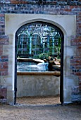 WATER FEATURE: ARCHWAY THROUGH TO STEW POND AND HERB GARDEN. THE ABBEY HOUSE  WILTSHIRE.