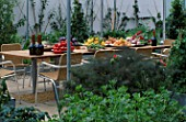 A PLACE TO SIT: WICKER SEATS WITH WINE   APRICOTS  TOMATOES  LEMONS AND PEAS ON THE TABLE. THE CHEFS ROOF GARDEN  CHELSEA 1999.