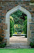 ARCHWAY IN BRICK WALL LOOKING THROUGH TO THE ROUND POND AND RECYCLING WATER TROUGHS. WITH ROSA IN THE BACKGROUND. THE ABBEY HOUSE  WILTSHIRE.
