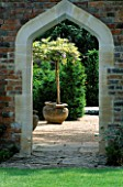 ARCHWAY IN BRICK WALL LOOKING THROUGH TO TERRACOTTA CONTAINERS HOLDING WISTERIA STANDARDS. THE ABBEY HOUSE  WILTSHIRE.