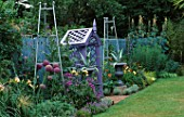 COVERED SEAT PAINTED MAUVE SURROUNDED BY METAL URNS PAINTED SILVER WITH AGAVES  SILVER METAL OBELISKS  ALLIUM CHRISTOPHII  HEMEROCALLIS  CARDOON AND ERIGERON. THE NICHOLS GARDEN