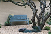 A PLACE TO SIT: LIGHT BLUE PAINTED BENCH WITH LILIUM REGALE  APPLE TREE & MAD EGG SCULPTURE BY AVANT GARDENER IN CLARE MATTHEWS GRAVEL GARDEN  READING.