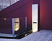 ROOF GARDEN WITH LIGHTING: TIMBER DECKING  RENDERED WALL PAINTED AUBERGINE  WATER FEATURE MADE FROM GALVANISED STEEL BLOCK AND SUNKEN RILL. DESIGNERS PAUL THOMPSON/TREVYN MCDOWELL