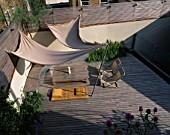 ROOF GARDEN: TIMBER DECKING  AWNING  DECKCHAIRS  SLATTED TRELLIS  KAUNA RUSH MATTRESS  WATER RILL  STEEL CONTAINER WITH GLOBE ARTICHOKES: DESIGNERS PAUL THOMPSON/TREVYN MCDOWELL