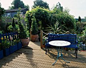 A PLACE TO SIT: BLUE BENCH & MOSAIC TABLE ON RIBBED DECKING. TWO TOPIARY BAY TREES LEAD TO TINY KITCHEN GARDEN. ROBIN GREEN & RALPH CADES SEASIDE STYLE GARDEN  LONDON.