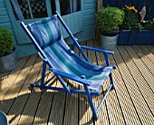 A PLACE TO SIT: BLUE STRIPED CANVAS DECKCHAIR ON RIBBED DECKING. IN B/G IS PAINTED SHED AND METAL CONTAINERS OF TOPIARY. ROBIN GREEN & RALPH CADES SEASIDE STYLE GARDEN  LONDON.