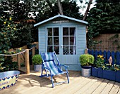 PAINTED BEACH HUT STYLE SHED STANDS BEHIND BLUE STRIPED CANVAS DECKCHAIR  PAINTED TIN BATH AND RIBBED DECKING. ROBIN GREEN AND RALPH CADES SEASIDE STYLE GARDEN  LONDON.