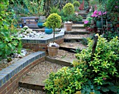 WOODEN SLEEPERS EDGE STEPS THROUGH THE GARDEN WITH STANDARD CLIPPED TREES AND OLD GARDEN TOOLS LINING THE PATH. ROBIN GREEN AND RALPH CADES SEASIDE STYLE GARDEN  LONDON.