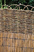 SPLIT BAMBOO AND WOVEN WILLOW PANEL CREATES STRONG VERTICAL AND HORIZONTAL LINES . ROBIN GREEN AND RALPH CADES SEASIDE STYLE GARDEN  LONDON.
