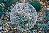 DETAIL OF AN ALUMINIUM GLOBE STANDING ON GRAVEL . ROBIN GREEN AND RALPH CADES SEASIDE STYLE GARDEN  LONDON